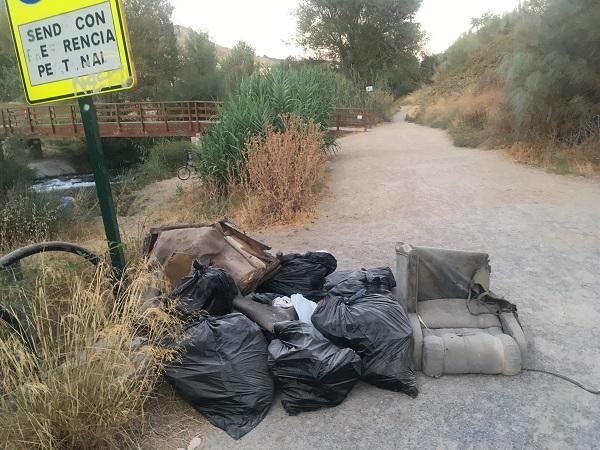 Basura y muebles acumulados en el sendero.