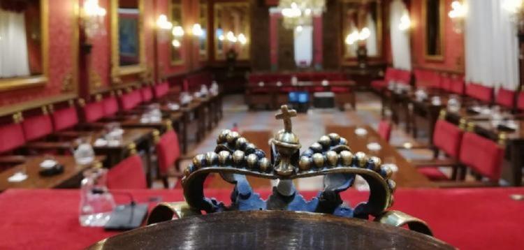 Salón de plenos vacío, con la silla de alcalde en primer plano.