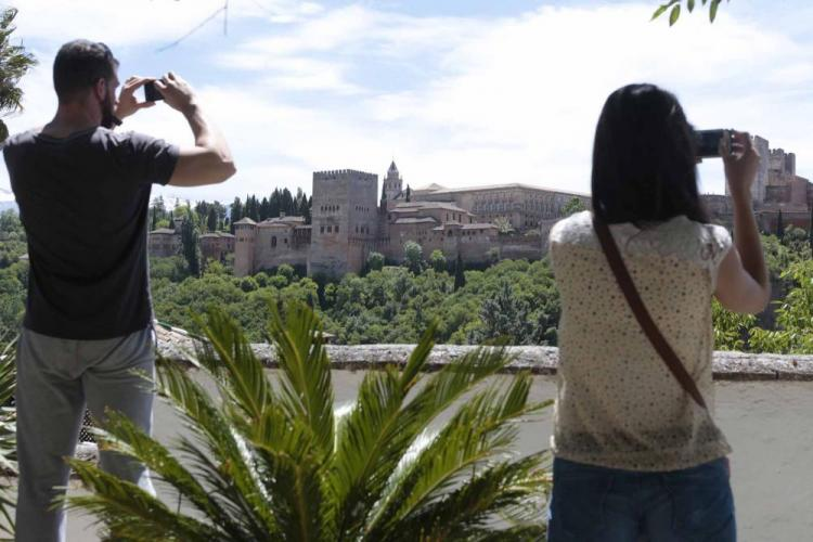 Unos turistas fotografían a la Alhambra desde el mirador de San Nicolás.