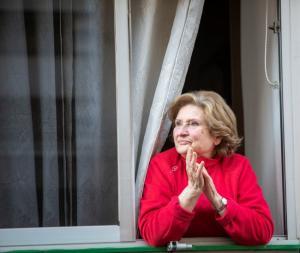Una mujer, aplaude desde su ventana a las ocho de la tarde.