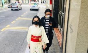 Dos japoneses pasean por una calle de Granada protegidos con mascarillas.