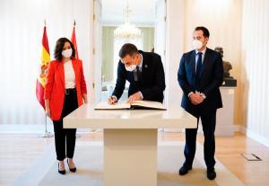 Pedro Sánchez firma en el libro de honor de la Comunidad de Madrid, ante Isabel Díaz Ayuso e Ignacio Aguado.