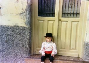 El autor, vestido de flamenco con motivo del Corpus o del Día de la Cruz, sentado en la puerta de la casa de sus abuelos, en Parrilla, nº 20 (hacia 1988-1989).