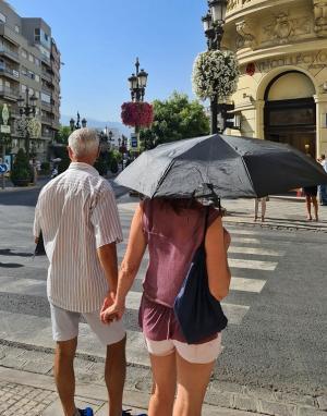 Una mujer se protege del sol con un paraguas en Puerta Real.