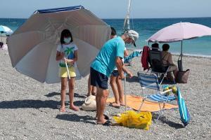 Bañistas en Playa Granada cumpliendo con el uso de mascarilla.