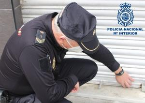 Un agente examina la persiana de un local.