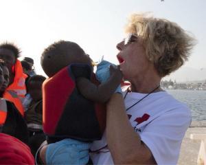 Una voluntaria de Cruz Roja, con uno de los bebés rescatados este lunes.
