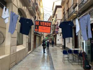 Ropa de empleados de hostelería y cartel colgados en la calle Navas en protesta por las restricciones.