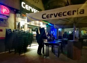 Un camarero recoge el mobiliario de la terraza de un establecimiento del Zaidín, poco antes de las 22.00 horas.
