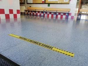 Señalización de distancia de seguridad en la entrada a un centro educativo.