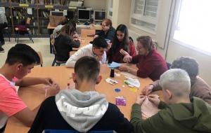 Adolescentes aprenden a coser durante el taller.