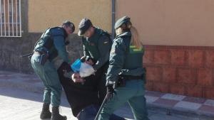 Agentes arrastran a una persona junto a la vivienda desalojada.