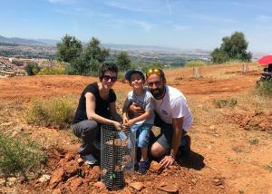 Una familia posa con la encina que ha plantado.