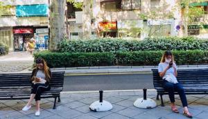Dos jóvenes, sentadas con mascarilla, observan sus teléfonos móviles