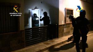 Agentes entran en un domicilio durante la operación policial.