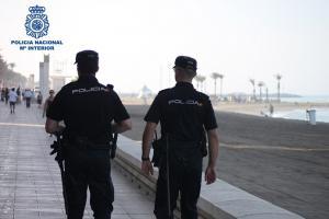 Agentes policiales patrullan por una playa.