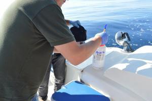 Un agente toma muestras del agua.