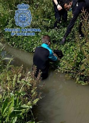 Un policía tiende la mano al hombre, hundido en la acequia, para ayudarle a salir.