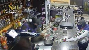 Uno de los atracadores golpea al responsable de un bar.
