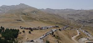 Zona de la Hoya de la Mora, llena de vehículos, con el Veleta al fondo a la izquierda.