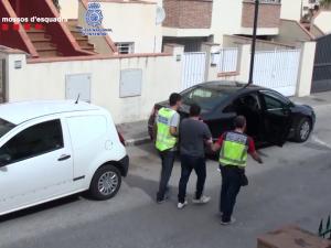 Los agentes trasladan a uno de los detenidos tras el registro de la vivienda.