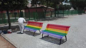 Dos de los bancos pintados con la bandera arcoíris.