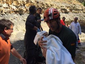 Uno de los guardias lleva en brazos al bebé, tras el rescate.