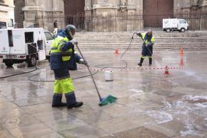Operarios de Inagra limpiando las pintadas en el pavimento del entorno de la Catedral.