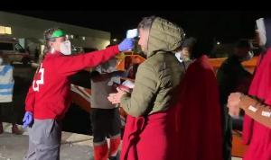 Una voluntaria de Cruz Roja toma la temperatura a los migrantes al desembarcar.