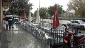 Terrazas cerradas y paraguas para la lluvia, este martes por la tarde.