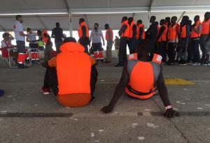Migrantes rescatados aguardan a ser atendidos por voluntariado de Cruz Roja en el Puerto de Motril.