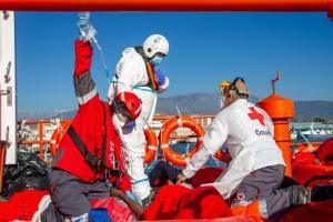 Personal de Salvamento Marítimo y de Cruz Roja atiende a uno de los migrantes rescatados.