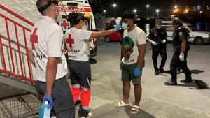 Voluntarios de Cruz Roja toman la temperatura a uno de los migrantes.