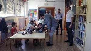 El delegado de Educación saluda a una de las personas mayores que interactúan con los escolares.