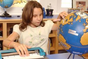 Una niña ciega en clase de geografía.
