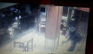 Uno de los delincuentes, con un hacha, en un bar.