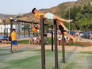 Jóvenes realizan ejercicios con barras en la nueva zona de gimnasia.