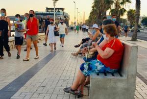 Mujeres sentadas, mientras otras personas pasean cerca de la playa, todas y todos con mascarilla.