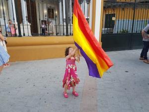 Una pequeña sostiene una bandera republicana, a las puertas de la Basílica de la Macarena, en Sevilla.