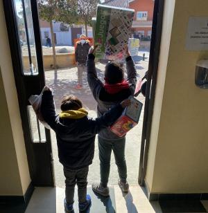 Dos niños salen de las dependencias municipales con sus juguetes.