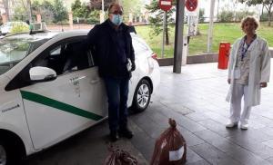 Un taxista solidario recibe el material de una integrante del Banco de Leche.