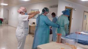 Profesionales del Virgen de las Nieves se colocan la indumentaria de seguridad.