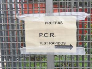 Cartel en un centro sanitario señalizando las pruebas PCR.