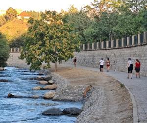 Paseantes por uno delos tramos urbanos del río Genil en Granada.