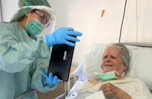 Una paciente habla con familiares mediante una tablet en el antiguo Clínico.