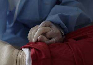 Una trabajadora de un Centro de Mayores sujeta la mano de un residente.