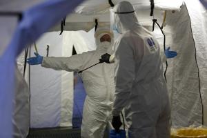 Personal de Protección Civil se desinfectan en la carpa del PTS.