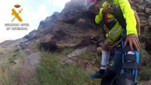 Un agente lleva a un accidentado, con una pierna inmovilizada.