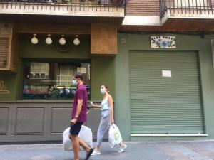 Una pareja, con mascarillas, en una barriada de la capital.