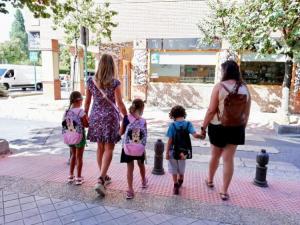 Tres alumnos con sus madres Tres escolares, con sus madres, se dirigen a su centro escolar en la capital.